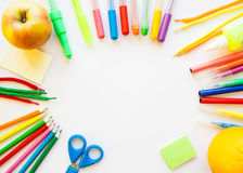 Stationery on the white background. Multicolor pencils and crayons, apple and orange. Place for your text Stock Photography