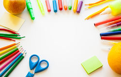 Stationery on the white background. Multicolor pencils and crayons, apple and orange. Place for your text Stock Photos