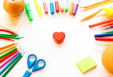 Stationery on the white background. Multicolor pencils and crayons, apple and orange. Red heart Stock Photos