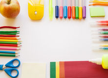 Stationery on the white background. Multicolor pencils and crayons, apple. Place for your text Stock Image