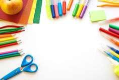 Stationery on the white background. Multicolor pencils and crayons, apple. Place for your text Royalty Free Stock Photos