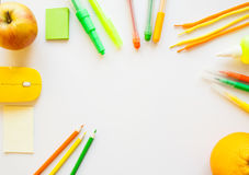 Stationery on the white background. Yellow, orange and green pencils and crayons, apple and orange. Place for your text Stock Photos