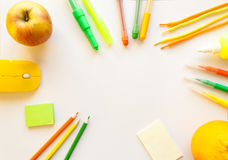 Stationery on the white background. Yellow, orange and green pencils and crayons, apple and orange. Place for your text Royalty Free Stock Image