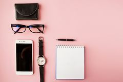 Stationery, white smartphone, glasses, pen, wallet, watch, calendar, notebook. Pink background. royalty free stock photography