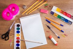 Stationery on a wooden table. Notebook, pens, pencils, paints, scissors, paper clips, eraser, pencil sharpener, glue and brush on. A wooden surface. Flat lay stock photo