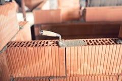 Stationieren Sie Baudetails und Werkzeuge, Kelle, Kittmesser auf Ziegelsteinschicht auf Innenwänden Stockfotografie