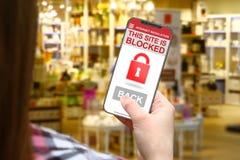 Stationieren Sie blockierte Idee, Mädchen mit frameless Telefon auf unscharfem Shophintergrund Lizenzfreies Stockfoto