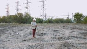 Stationieren Sie technischen Direktor mit Ausführungszeichnung am Atomkraftwerk Arbeitskraft im weißen Sturzhelm mit Technik stock video