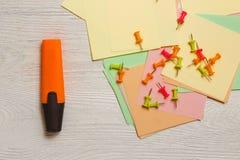 Stationnaire, punaises sur les autocollants, barre de mise en valeur orange sur le fond en bois blanc Concept de stratégie de pla Image libre de droits