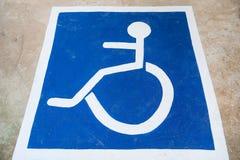 Stationnement blanc et bleu de voiture de symbole d'handicap d'handicapé sur le plancher Images libres de droits