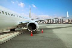 Stationnement d'avion de passagers dans la piste d'aéroport avec le backg urbain de scène Photos libres de droits
