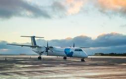 Stationnement motivé par le propulseur privé d'avion à l'aéroport avec le fond de coucher du soleil Photographie stock libre de droits