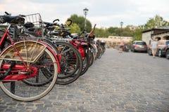 Stationnement pour des bicyclettes sur la rue Louez un vélo et une promenade autour de la ville photos libres de droits