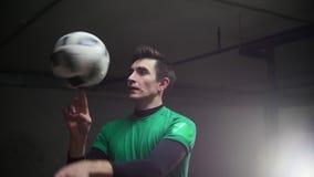 Stationnement souterrain Tours s'exerçants d'un football de jeune homme du football Rotation de la boule sur le doigt clips vidéos