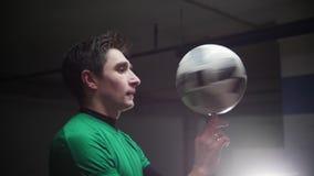Stationnement souterrain Un jeune homme du football tournant la boule sur son doigt banque de vidéos