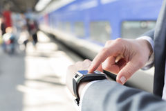 On stations platform a man using his smartwatch. Close-up hands Stock Photo