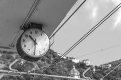 Stationsklocka i bergstaden, Sorrento Italien, tid att rida, svartvitt schema av transport royaltyfria foton