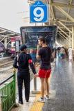 Stationspersonal, das einen Touristen unterstützt stockfotografie