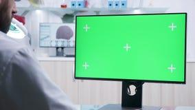 Statisch over de schouder die van arts wordt geschoten die aan de groene computer van het het schermprototype werken stock footage