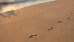Statisch zeer wijd geschoten van voetafdrukken in het zand op waimanalostrand Hawaï stock videobeelden