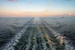 Statische Spur hinter baltischer Fähre im Sonnenunterganglicht stockfotos