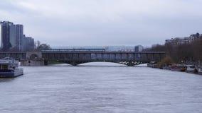 Statischer breiter Schuss eines Zugs, der über Pont de Bir-Hakeim während des Paris überschreitet, überschwemmt stock video
