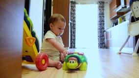 Statischer Schuss, nette sieben Monate alte Baby, die mit pädagogischen Spielwaren auf der glücklichen Kindheit des Bodens, frühe stock video footage