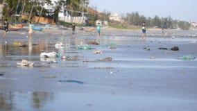 Statisk elektricitetskott av att spela barn i defocus på stranden som förorenas av avfall, avskräde lager videofilmer