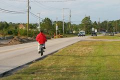 Statistic Waiting to Happen. A boy rides his bike along a busy two-way road where there is no sidewalk.  When he passed me, and I saw how close the cars were Stock Photography