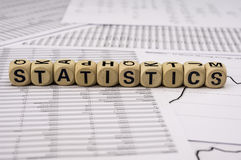 Statistical analysis sheets with the word statistics assembled with wooden letter blocks Stock Photos