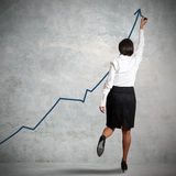 Statistics. Businesswoman drawing statistics in a wall Royalty Free Stock Photography