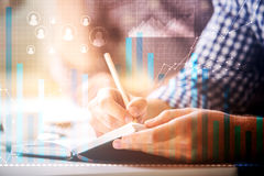 Statistics concept. Close up of male hands writing something in notepad placed on office desktop with abstract digital business charts. Statistics concept Royalty Free Stock Photos