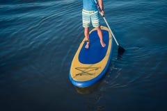 Stativ paddlar upp stiger ombord manen som paddleboarding royaltyfri bild