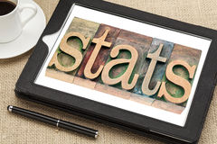 Stats (statistics) in wood type. Stats (statistics) - a word in vintage letterpress wood type printing blocks on a digital tablet with a cup of coffee stock image