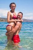 Stattliche lächelnde Paare, die im Wasser umarmen Stockfotografie