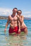 Stattliche Paare, die im Wasser umarmen Stockbilder