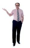 Stattlicher älterer Chef, der mit einer geöffneten Palme aufwirft stockbilder