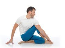 Stattlicher aktiver Mann, der Yogaeignunghaltungen tut Stockfoto