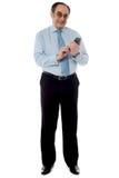 Stattlicher alter Unternehmensmann, der Mobiltelefon verwendet stockfoto