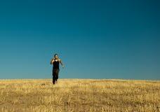 Stattlicher asiatischer Mann, der innen in die Gerstenwiese läuft Stockfoto