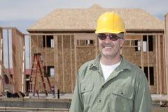 Stattlicher Bauarbeiter, der ein Haus aufbaut stockbild
