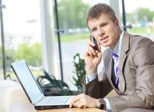 Stattlicher Geschäftskerl, der an Mobiltelefon und Schoss arbeitet Stockfoto