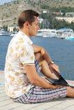 Stattlicher Geschäftsmann, der durch das Meer sitzt Lizenzfreie Stockfotos