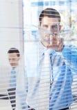 Stattlicher Geschäftsmann, der durch Vorhänge lugt Lizenzfreies Stockfoto