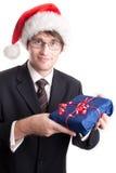 Stattlicher Geschäftsmann, der ein Weihnachtsgeschenk anbietet Stockfoto