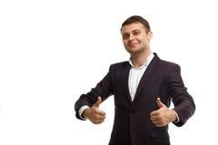 Stattlicher Geschäftsmann, der sich Daumen zeigt Stockbild