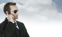 Stattlicher Geschäftsmann mit Sonnenbrillen und bluetooth Lizenzfreies Stockfoto
