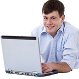 Stattlicher, glücklicher Mann, der auf Fußboden mit Computer liegt Stockbild