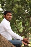 Stattlicher indischer Mann, der unter einem Baum meditiert Lizenzfreies Stockbild