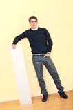 Stattlicher junger Geschäftsmann, der auf leerem Blatt sich lehnt stockfotografie